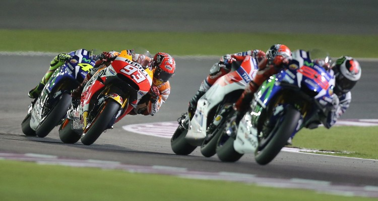 Spanish rider Marc Marquez (2L) of Repsol Honda Team competes to win third place in the Qatar Moto Grand Prix race on March 20, 2016 at the Losail International Circuit in the Qatari capital Doha. Spanish driver of Movistar Yamaha MotoGP Jorge Lorenzo won the Qatar MotoGP. / AFP PHOTO / KARIM JAAFAR