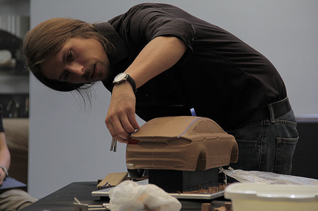 Artista modelando coche de arcilla